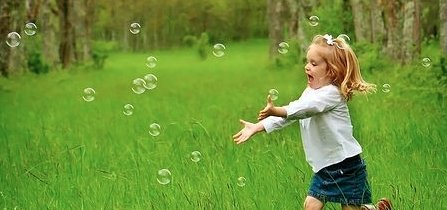 A little girl playing with water bubbles