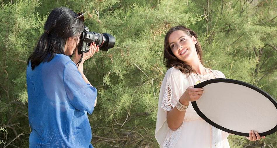 Women getting herself photographed while holding a reflector
