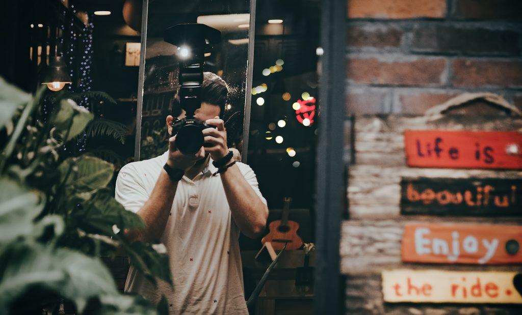 guy taking photographs in street
