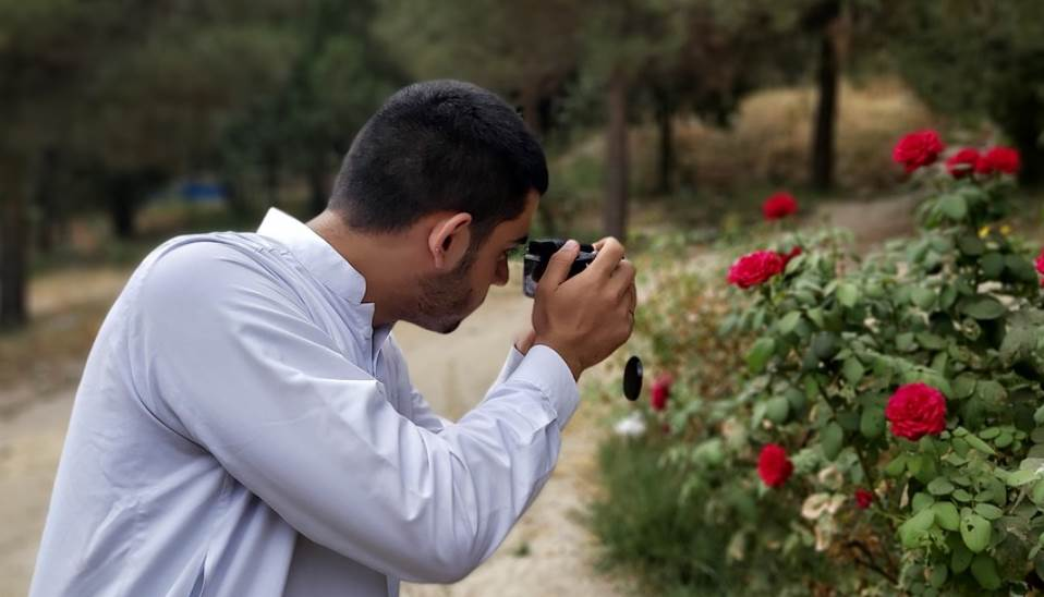 image of a person getting photo of rose