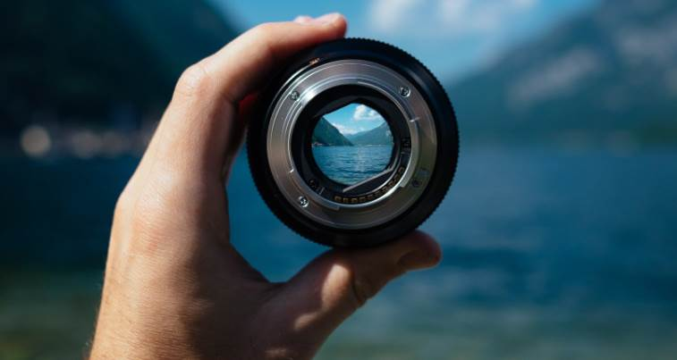 image of a person holding the camera lens