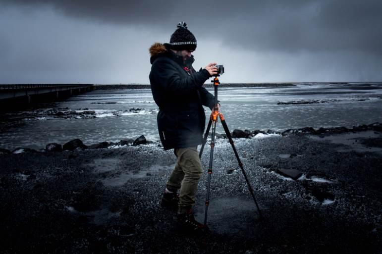 person taking a photo near frozen lake
